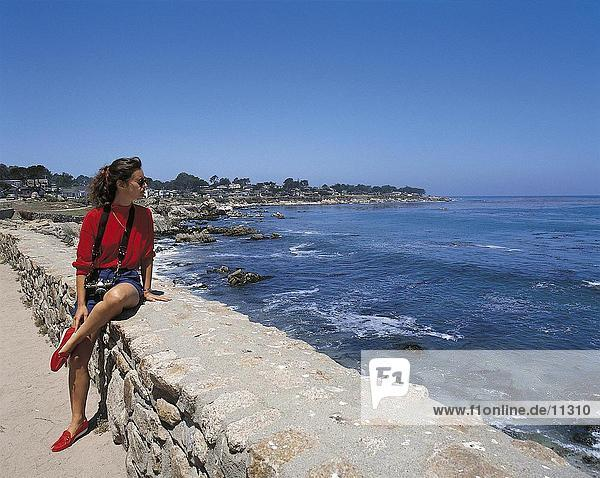 Woman sitting on wall by the sea  Monterey  California  USA