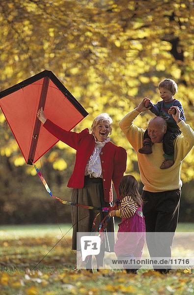 älteres Paar spielen mit ihren Enkelkindern in einem park