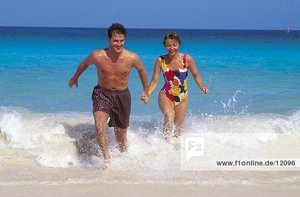 Young couple running in water on beach