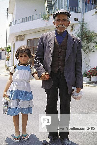 Portrait of senior man standing with his granddaughter on road  Greece