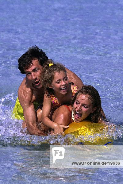 Familie auf eine aufblasbare Fisch im Wasser liegen