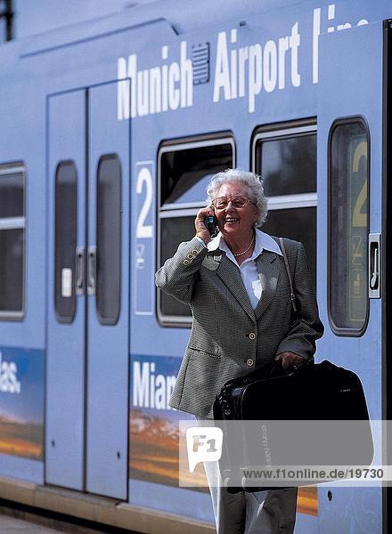 Frau Gespräch auf Handy am Bahnhof