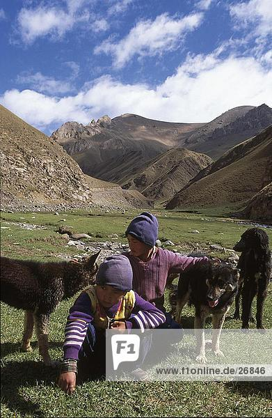 Children crouching on landscape with dog  Kirgistan