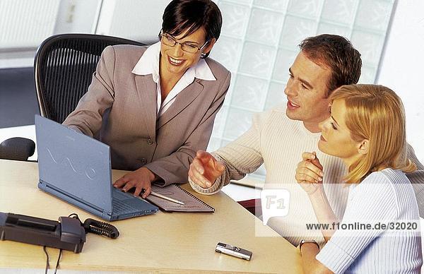 Geschäftsfrau und ein junges paar Blick auf einem laptop