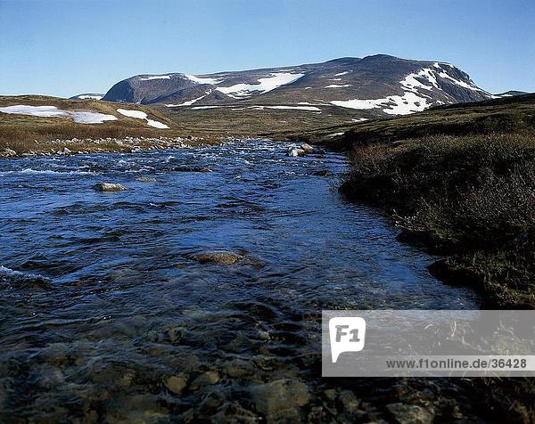 River flowing through a landscape with mountains in the background  Dovre National Park  Norway