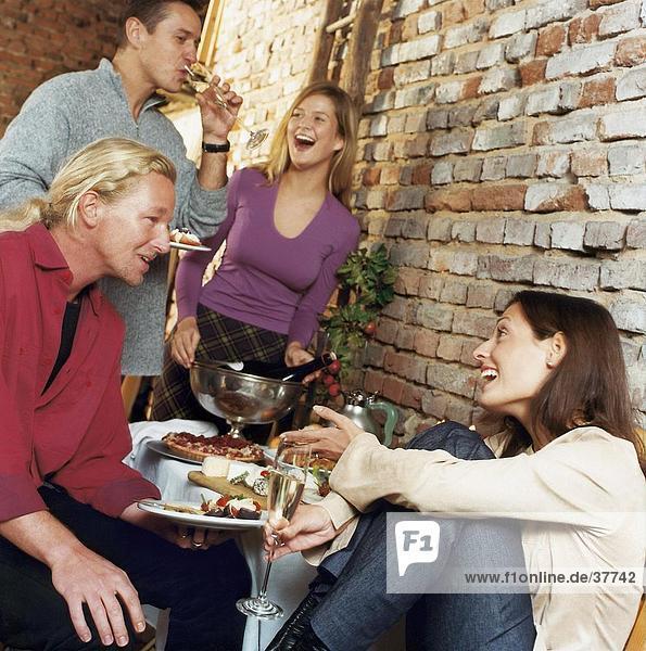 Zwei junge Paare lächelnd bei Tisch
