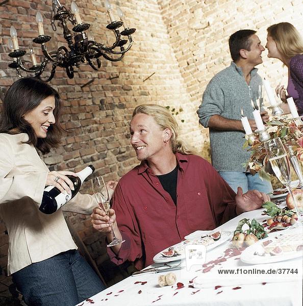 Junge Frau Gießen Champagner in ein junger Mann Glas