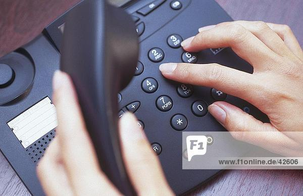 Close-up of woman's hands dialing landline phone