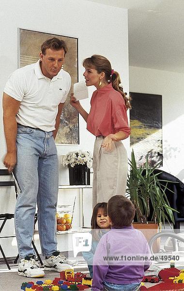 Zwei Kinder mit ihren Eltern hinter ihnen miteinander zu reden auf Boden spielen