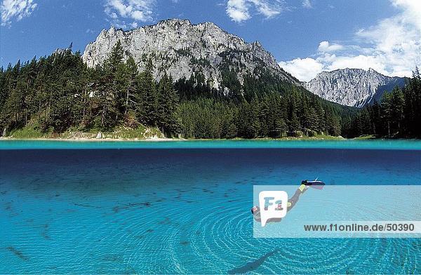 Tauchend in See mit Berg im Hintergrund  alpinen See  Österreich Tauchend in See mit Berg im Hintergrund, alpinen See, Österreich