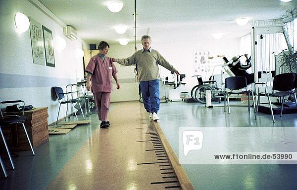 Physiotherapeutin helfen älterer Mann zu Fuß in Rehabilitationszentrum