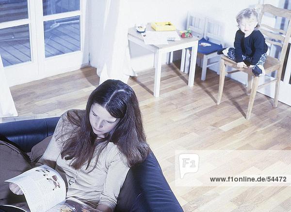 Erhöhte Ansicht von Frau Lesung Buch über Sofa mit ihrem Kind sitzt auf Stuhl im Hintergrund