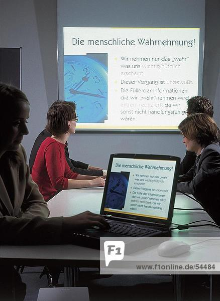 Businessman using laptop with his colleagues looking at projection screen in background