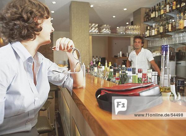 Junge Frau schauen  Barkeeper und lächelnd