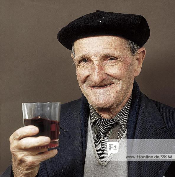 Portrait of senior man holding glass of red wine  Spain  Europe