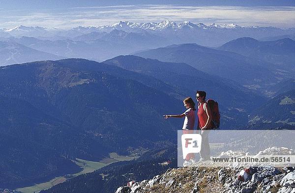Mädchen stehen auf einem Berg mit einer Frau und zeigen