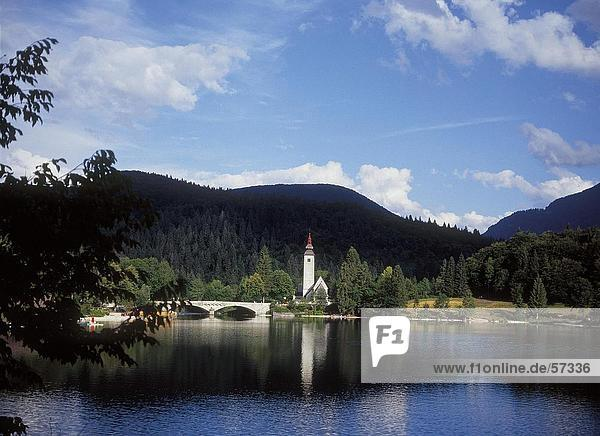 Brücke über einen Fluss führt zu einer Kirche  Bohinj See  Nationalpark Triglav  Slowenien