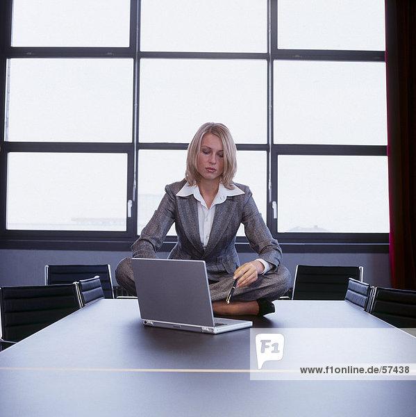 Geschäftsfrau sitzt mit Laptop an einen Konferenztisch