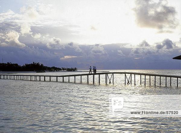 Drei Menschen stehen auf einer Brücke  Malediven