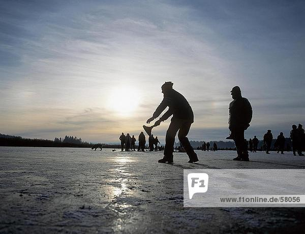 Silhouette von Menschen spielen Curling auf zugefrorenen See  dem Chiemsee  oberen Bayern  Bayern  Deutschland