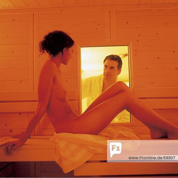 Nackte Frau sitzen im Sauna und Man durch Fenster Suchen
