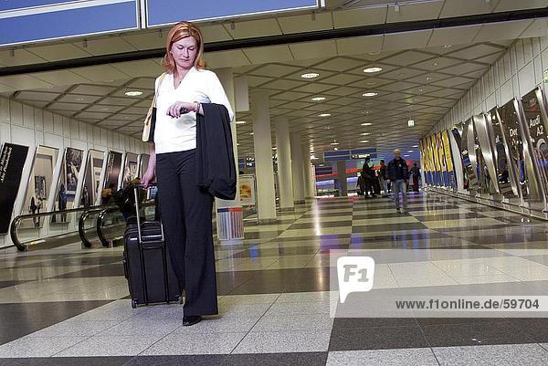 Geschäftsfrau ziehende Gepäck am Flughafen