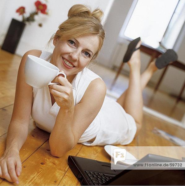 Frau auf Boden liegen und Kaffee zu trinken