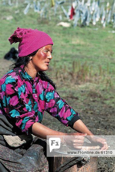China  Tibetisch  Frau sitzt mit Eimer