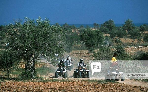 Quad bikers racing on dirt road  Djerba  Tunisia