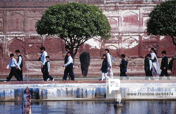 Schulkinder zu Fuß neben Teich  Lahore  Pakistan