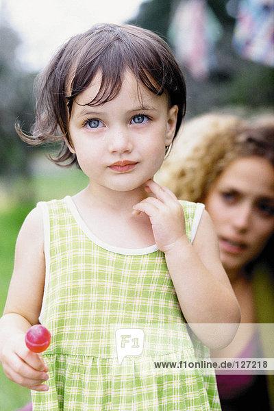 Kleines Mädchen mit Mutter im Hintergrund