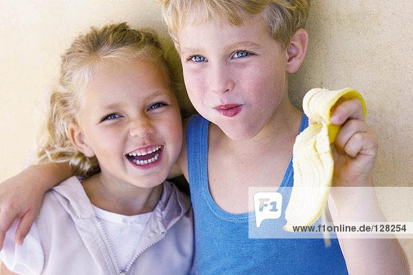 Junge umarmt Schwester und isst Banane