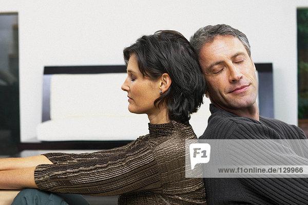 Mann und Frau lehnen sich aneinander.