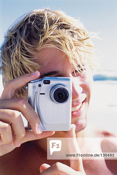 Man with camera on beach