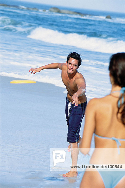 Man and woman playing frisbee on the beach