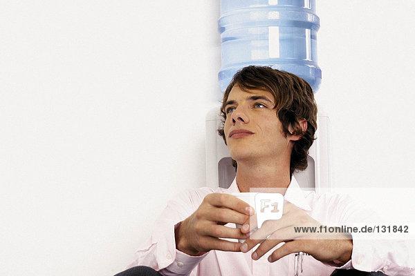 Geschäftsmann sitzt neben dem Mineralwasser