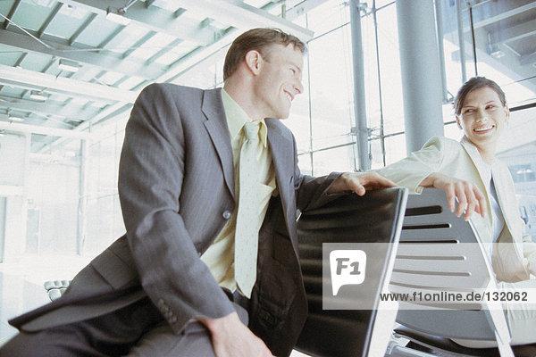 Geschäftsmann und Geschäftsfrau treffen sich in der Airport Lounge