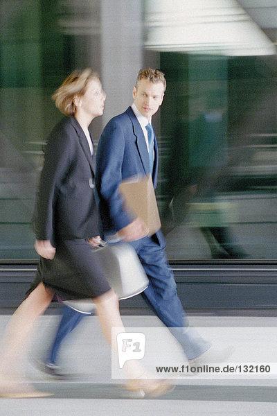 Geschäftsmann und Geschäftsfrau gehen zügig voran