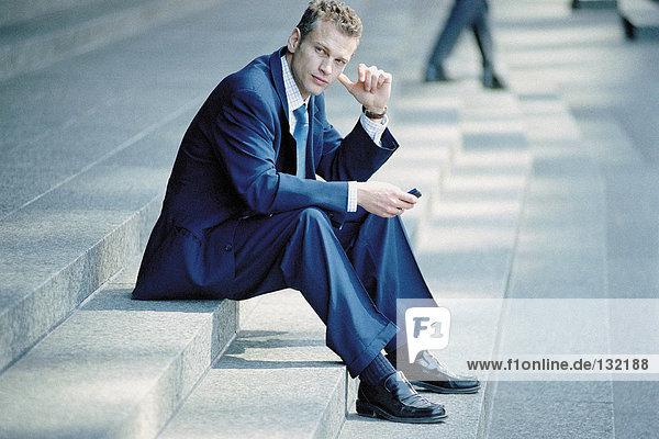 Geschäftsmann auf der Treppe sitzend mit Handy Geschäftsmann auf der Treppe sitzend mit Handy