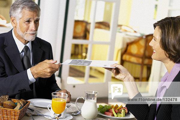 Geschäftsmann und Geschäftsfrau  die beim Frühstück Geschäfte machen