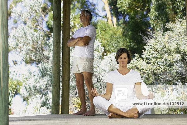 Frau beim Yoga draußen mit stehendem Mann