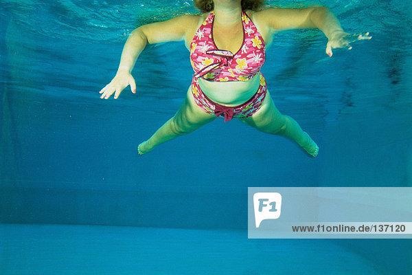 Eine Frau tanzt unter Wasser