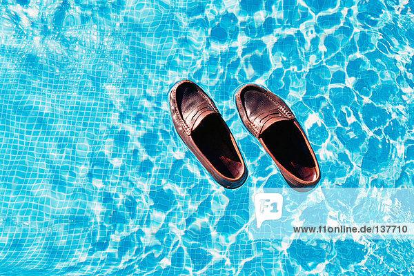Schwimmende Schuhe im Schwimmbad