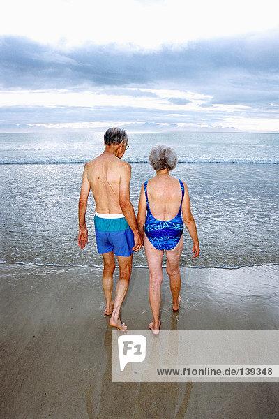 Ein reifes Paar  das am Strand baden geht.