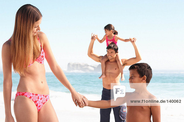 Mama und Sohn halten sich am Strand an den Händen.