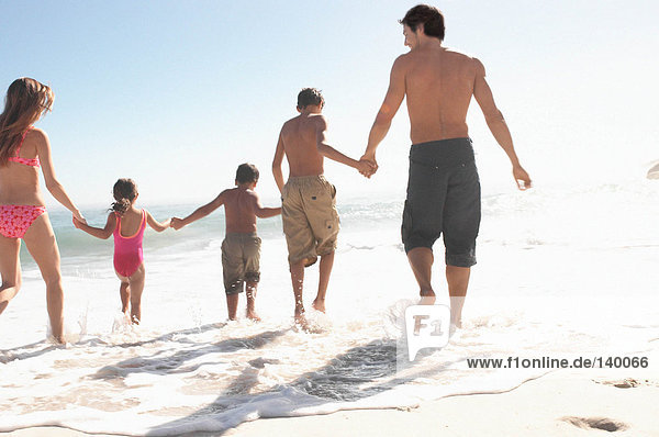 Familie beim Spaziergang ins Meer
