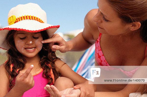 Mama trägt Sonnencreme auf das Gesicht der Tochter auf.