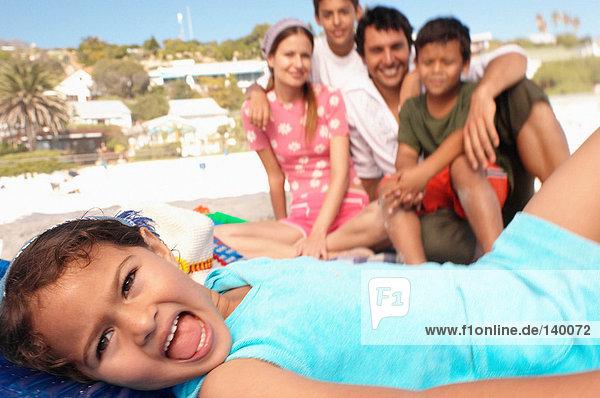 Mädchen am Strand mit Familie im Hintergrund