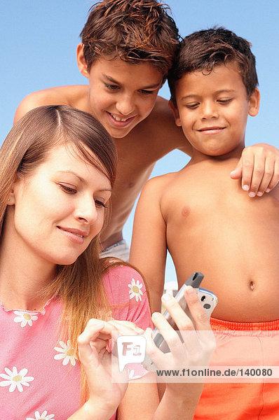 Mutter und Söhne mit Handy