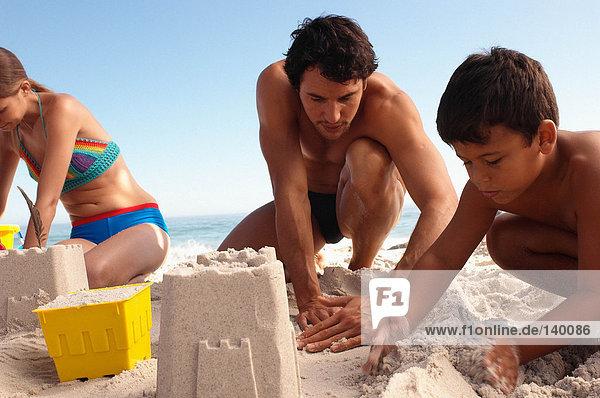 Vater und Sohn beim Bau einer Sandburg